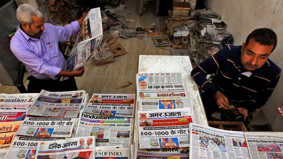 A man reads a cover story in a daily national newspaper at a roadside stall in Allahabad.
