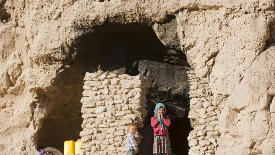 An Afghan girl, Shepha Qah, 8, and her brother stand by the door of their cave in Bamiyan. The cave-dwelling families of the province struggle to get by on the bare minimum. But even this bare-bones way of life is now under threat as the government relocates residents to pave the way for transforming the man-made grottoes into a global tourist destination. (AP)