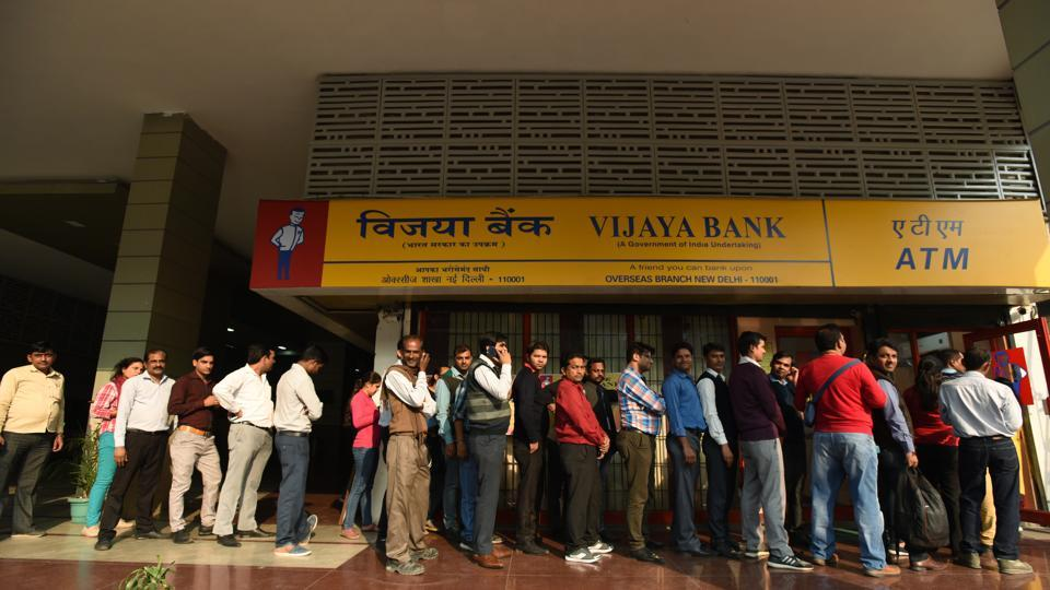 People wait outside an ATM to withdraw cash at K G Marg in New Delhi.