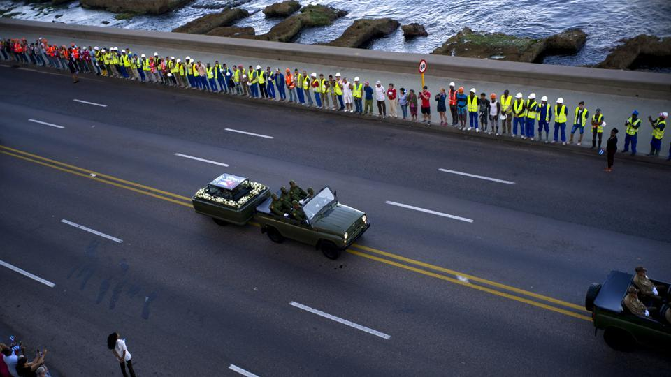 People line the Malecon seaside boulevard as they watch the motorcade transporting the remains of Cuban leader Fidel Castro in Havana, Cuba.