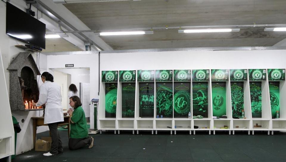 Employees of Chapecoense soccer team pray inside the team's locker room at the Arena Conda stadium in Chapeco, Brazil. A plane crash in Colombia wiped out almost the entire squad.