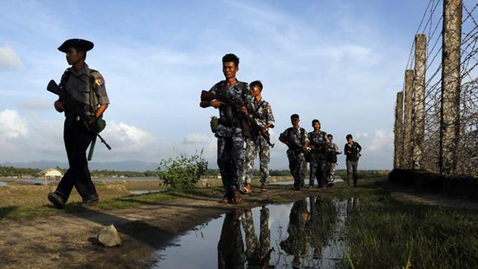 Myanmar police officers patrol along the border fence between Myanmar-China border.