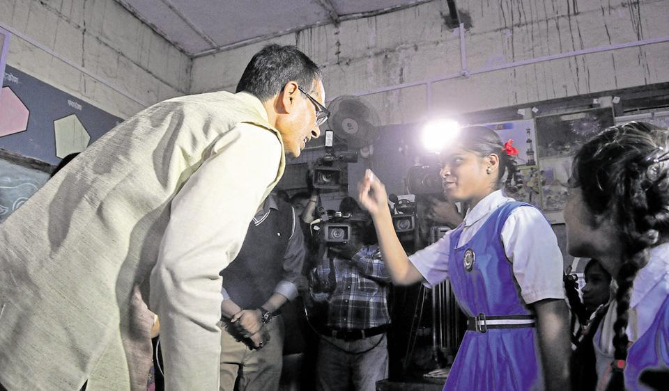 Chief minister Shivraj Singh Chouhan interacts with school students in Bhopal on Tuesday. The BJP marked the completion of Chouhan's 11 years in office as deepotsav, the festival of lights, and lit earthen lamps at public venues.