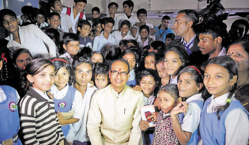 The chief minister with students at the government middle school on Tuesday. The CM had studied at this school. Mujeeb Faruqui/ht photo