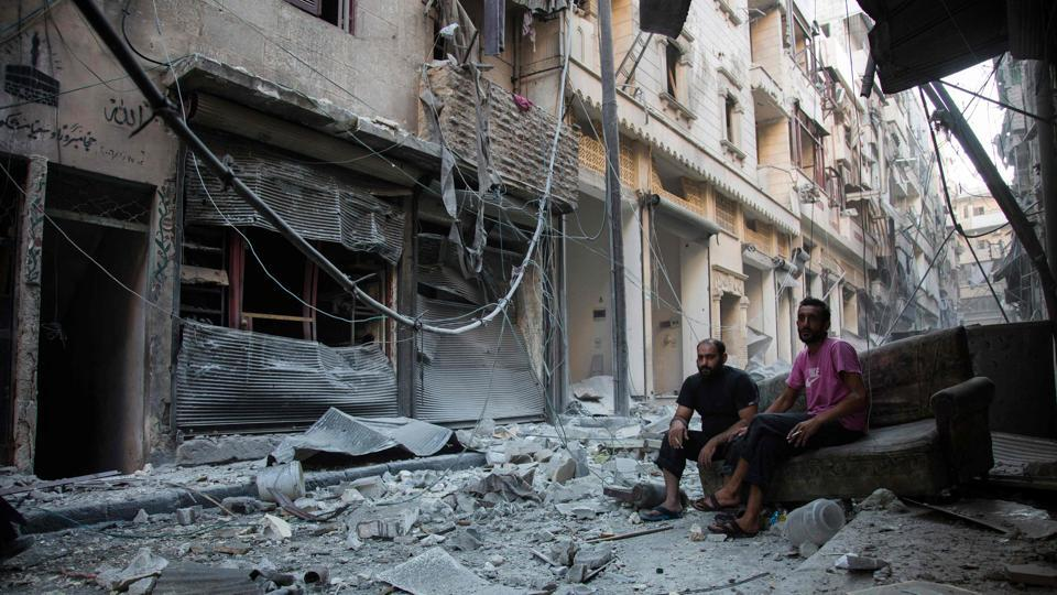 Syrians sit amidst rubble following an air strike on the rebel-controlled neighbourhood of Karm al-Jabal on September 18, 2016. Syria's ceasefire was on the brink of collapsing Sunday, after a US-led coalition strike killed dozens of regime soldiers and Aleppo city was hit by its first raids in nearly a week.