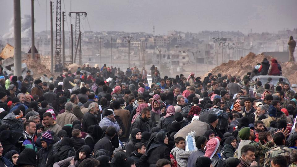 Syrian families, fleeing from various eastern districts of Aleppo, queue to get onto governmental buses in the government-held eastern neighbourhood of Jabal Badro.
