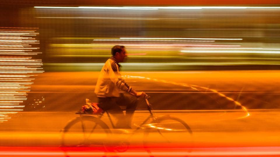 A man cycles on a brightly-lit road on a foggy evening in Amritsar. (Gurpreet Singh/HT)
