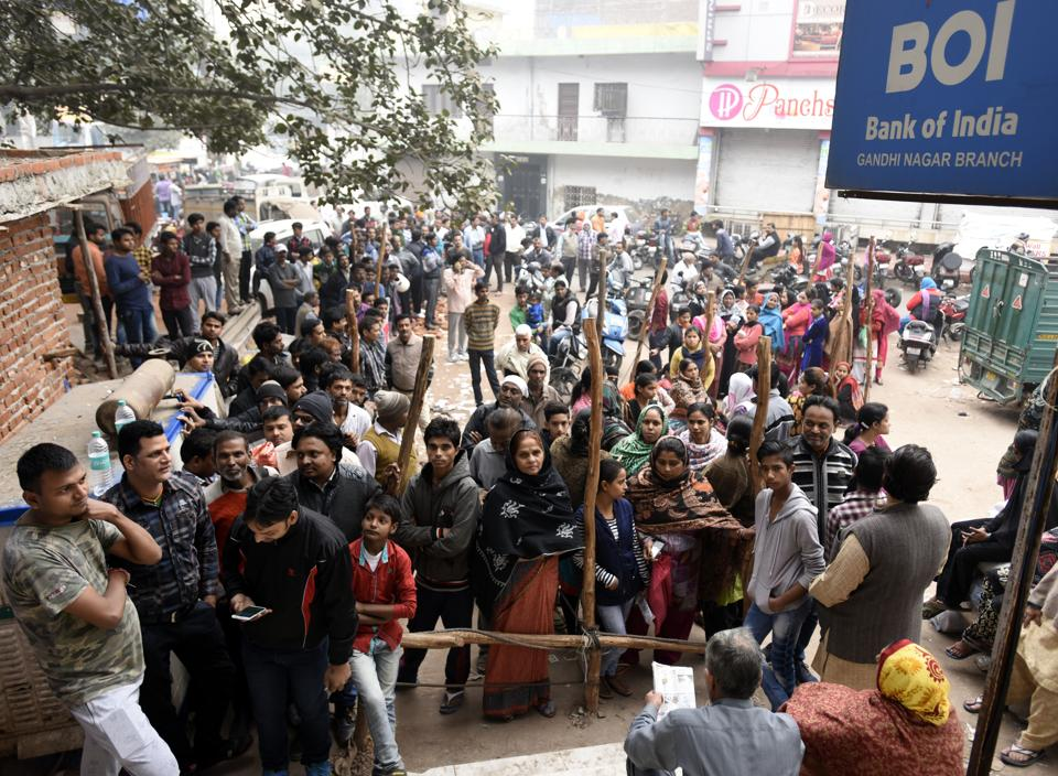 People wait outside a Bank of India branch at Jheel Chowk branch in New Delhi on Wednesday, November 30, 2016.