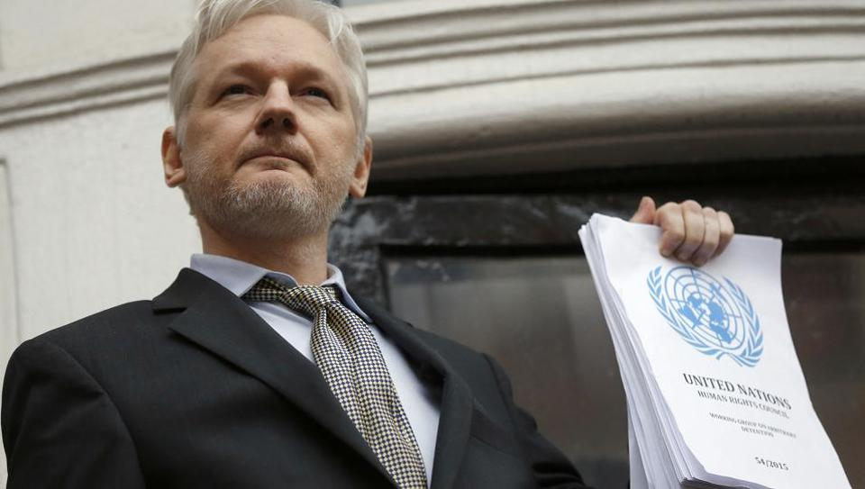 WikiLeaks founder Julian Assange holds a UN report as he speaks on the balcony of the Ecuadorean Embassy in London.