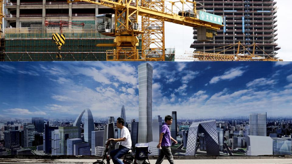 A man on a motorbike and a pedestrian pass by a construction site wall depicting the skyline of the Chinese capital in Beijing.