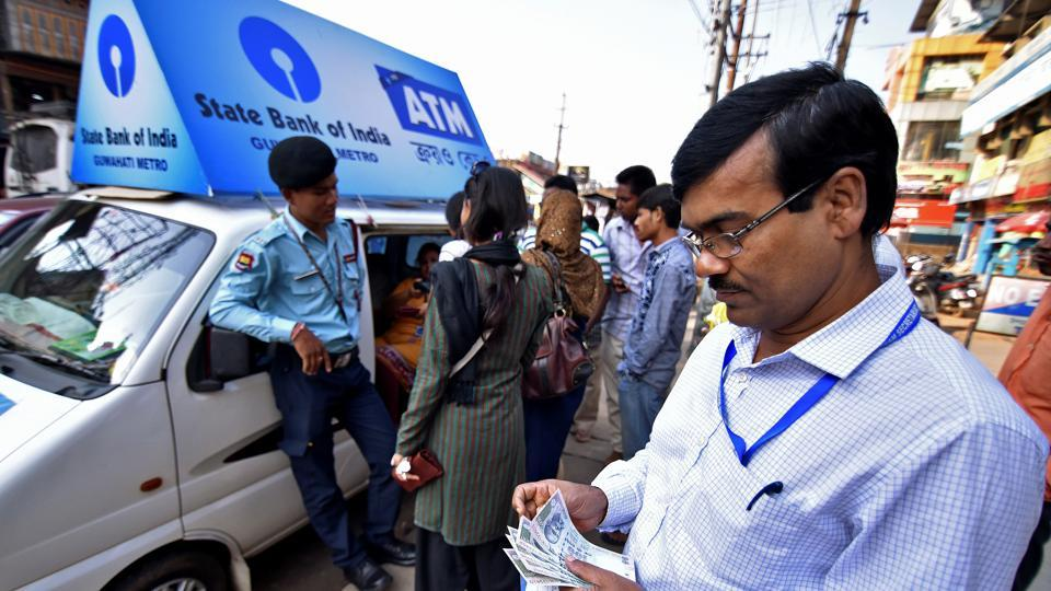 A man counts 100 Indian rupee banknotes after withdrawing them from a mobile ATM van in Guwahati on November 25.
