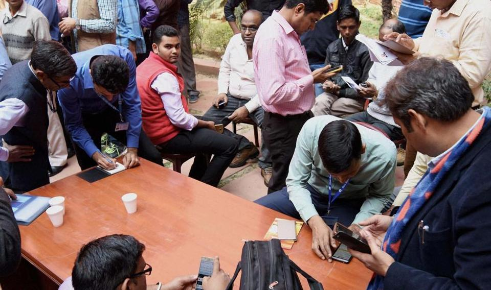 Bank employees train Finance Ministry staff for mobile banking and cashless transactions at North Block in New Delhi on Tuesday.
