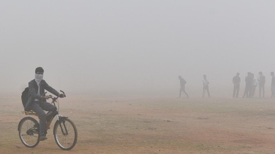School student covers his face to protect himself from pollution in New Delhi.