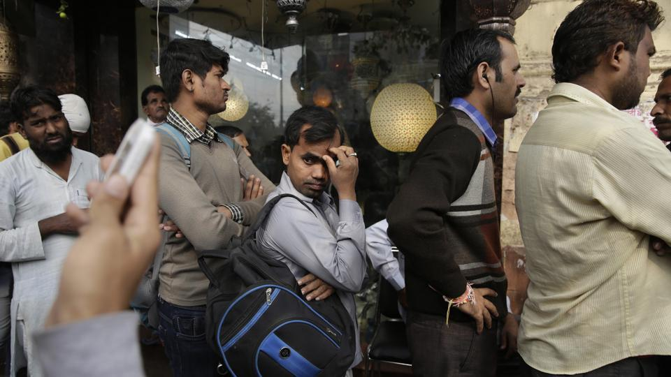 People stand in queue to withdraw money from a bank in Delhi on December 1, 2016.