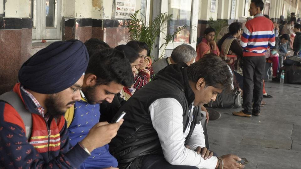 Passengers using free wi-fi at the railway station in Jalandhar on Thursday.