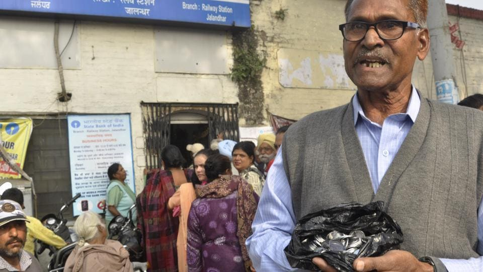 A senior citizen showing Rs 2 coins of Rs 100 value which he had withdrawn with cash from a bank in Jalandhar on Thursday.