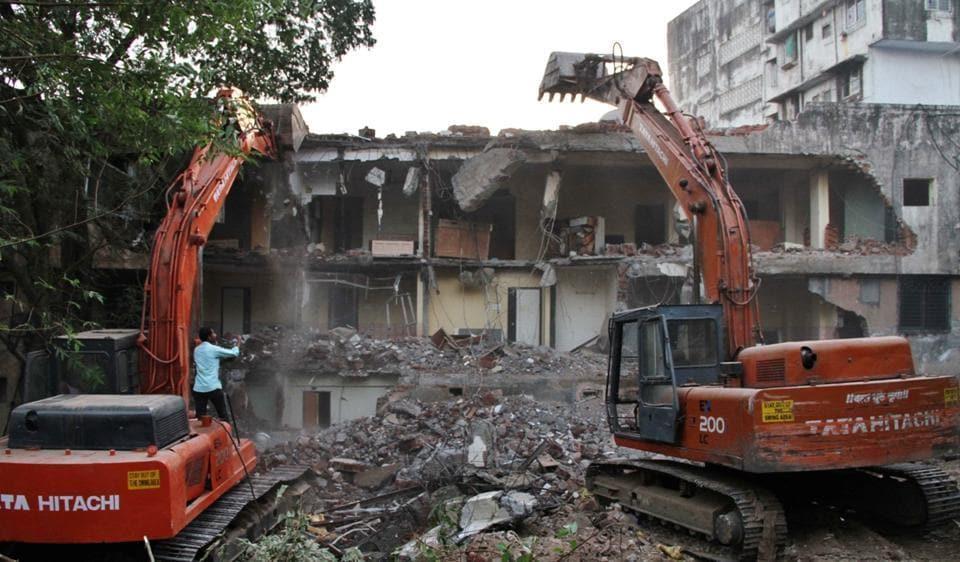 TMC workers demolish Satyam Lodge on Thursday.