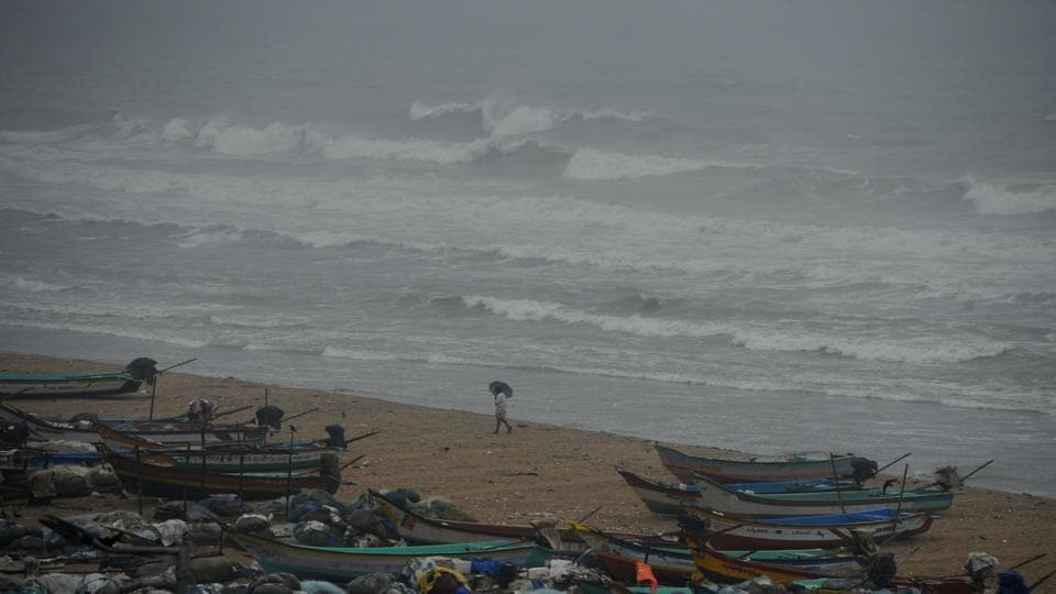 A fisherman walks near boats as waves break on the cost of the Bay of Bengal in Chennai before of Cyclone Nada makes landfall.