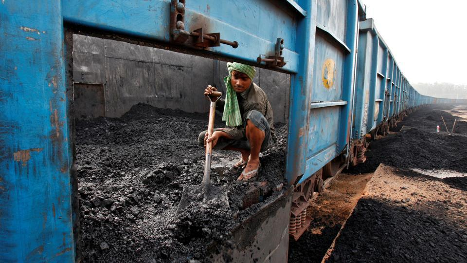 A worker unloads coal from a goods train at a railway yard in the northern city of Chandigarh.