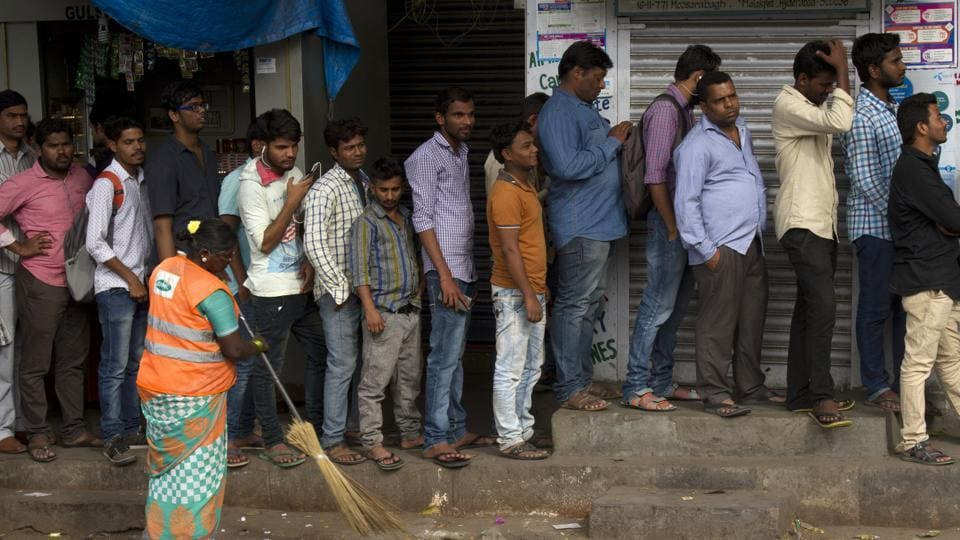 A state government employee who was returning home in Kolkata from his place of posting died while standing in a queue in front of an ATM .