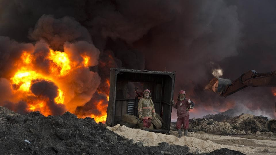 Firefighters work to quell an oil fire set by Islamic State militants in Qayara, south of Mosul, Iraq, on Monday, November 28, 2016.