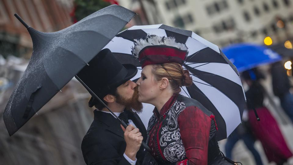 A couple kiss under their umbrellas at Dickens on The Strand in Galveston, Texas, on Saturday. Due to the inclement weather, organisers had to waive admission fees and later announce that the festival would be held again a week later.  (AP)
