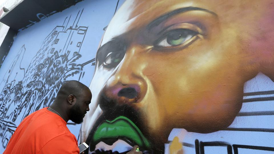 An artist works on a mural in the Wynwood Art District in Miami on , Friday, as part of the 15th Art Basel festival. (AP)