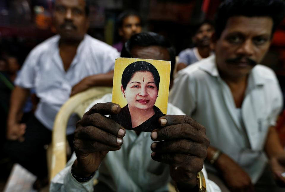 A supporter of Tamil Nadu chief minister Jayalalithaa holds her photo at the AIADMK party office in Mumbai.  (REUTERS)