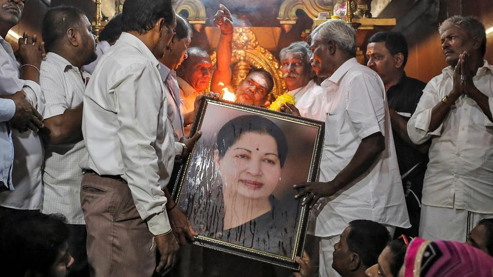 Well wishers of Tamil Nadu Chief Minister Jayalalithaa Jayaraman hold her portrait as they pray at a temple in Mumbai on December 5. (REUTERS)