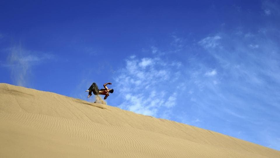 An Iranian man flips on the sands while enjoying his weekend in the desert. (AP)