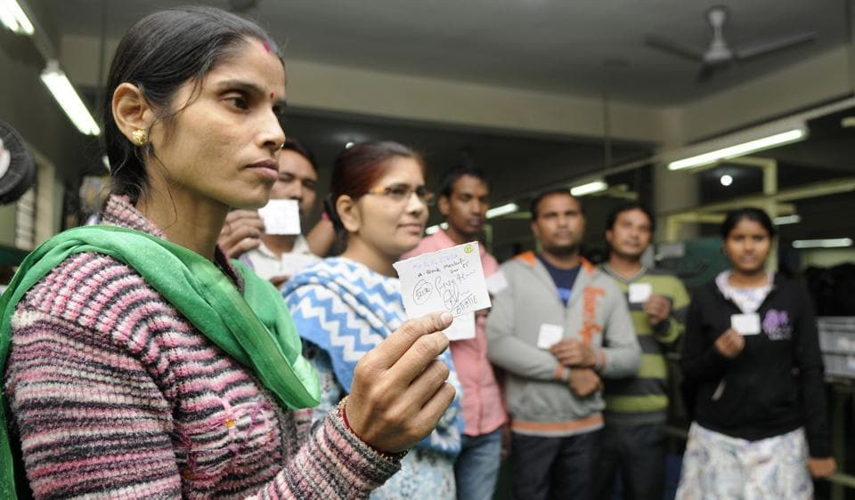 A worker holds up a coupon for purchase of goods worth Rs500 distributed at a factory, on Tuesday.