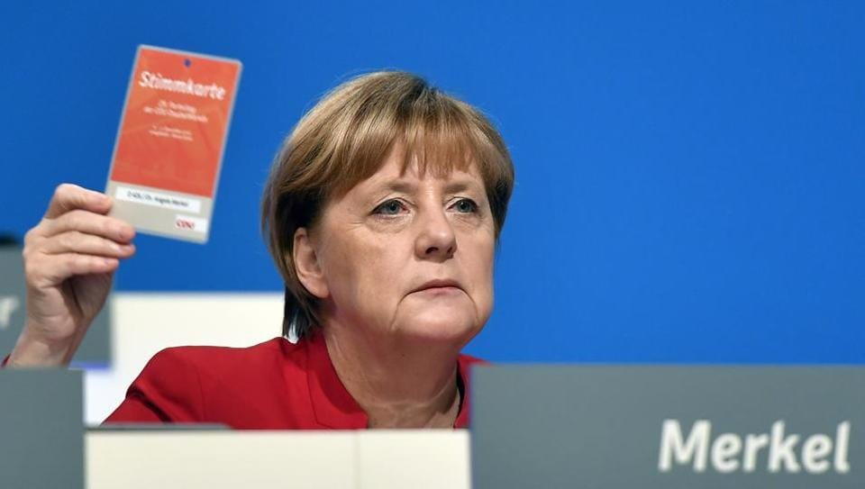 German Chancellor  holds an voting ticket during a party conference of the Christian Democratic Union (CDU) in Essen, Germany, Tuesday, Dec. 6, 2016.