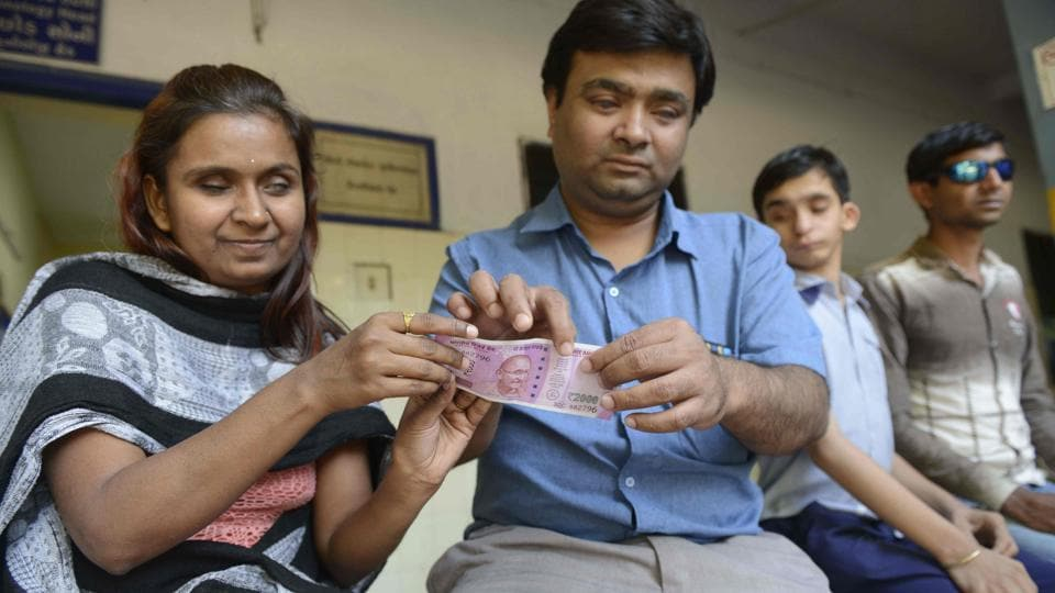 Visually impaired teacher from shows a visually impaired girl how to identify a new 2000 rupee note at the Blind People's Association in Ahmedabad.