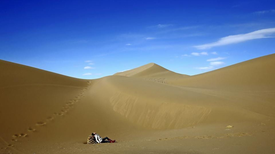 An Iranian woman relaxes on the sands. Mesr desert and its oasis are known as Dashte-Kavir in Persian. (AP)