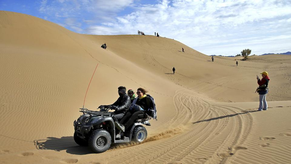 Iranian youths riding a quad bike in the desert. There is a spring that flows out of the foothills of these mountains. (AP)