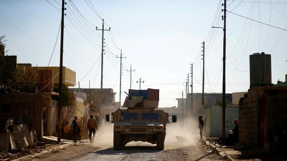 A vehicle of Iraqi army drives in the street during a battle with Islamic State militants in the neighbourhood of Intisar, eastern Mosul, Iraq, December 6, 2016.