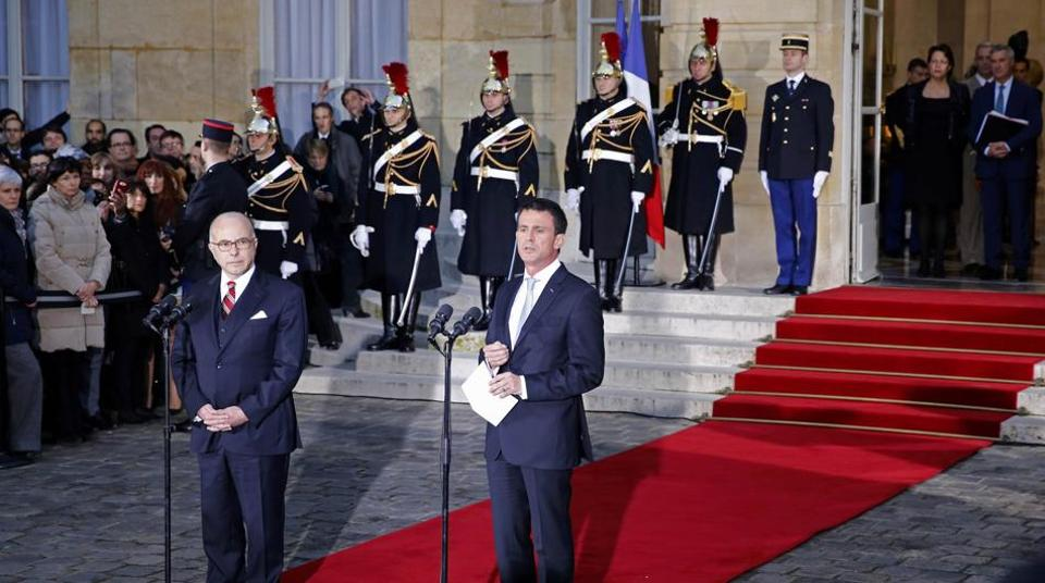 Outgoing French Prime Minister Manuel Valls (R) delivers a speech next to newly-appointed Prime Minister Bernard Cazeneuve during the official handover ceremony at the Hotel Matignon in Paris on December 6.