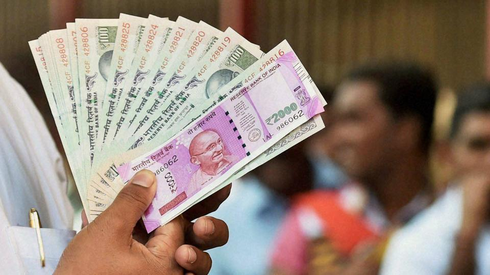 A man showing his new Rs 2000 notes with 100-rupee notes as others queue up to change their notes at outside RBI in Mumbai.