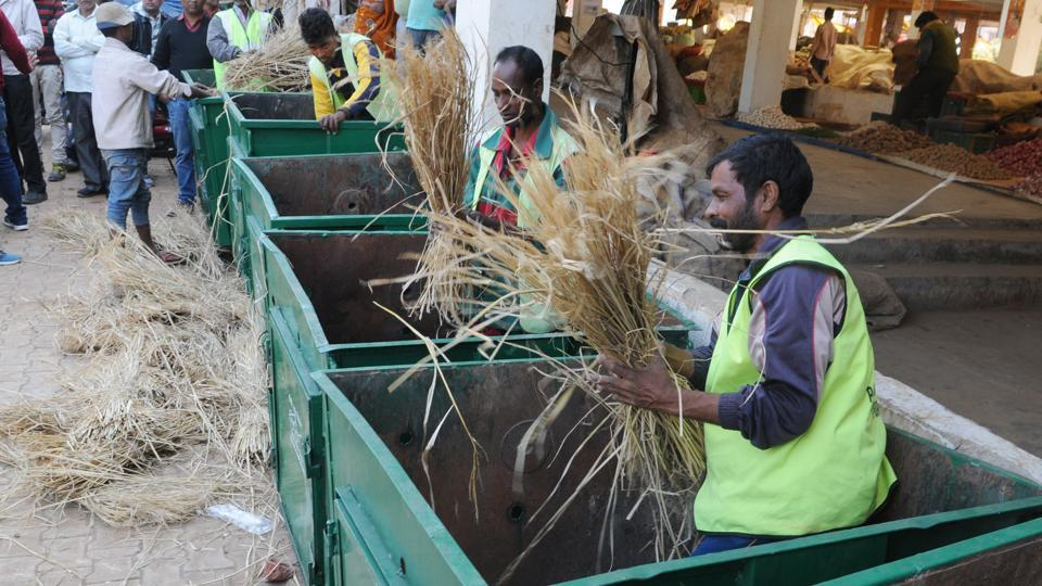 Ranchi Municipal Corporation staff spreading paddy straw in boxes where vegetable waste will be dumped to prepare organic fertilizer at Khadgarha vegetable market on Tuesday.