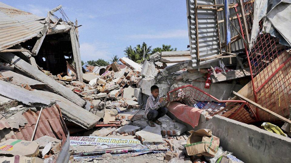 A boy sits on the rubble of a building that collapsed after an earthquake as he takes shelter from the sun in Pidie Jaya, Aceh province, Indonesia, on Wednesday. The 6.5-magnitude quake rocked Aceh province early on Wednesday, killing nearly 100 people and causing dozens of buildings to collapse.