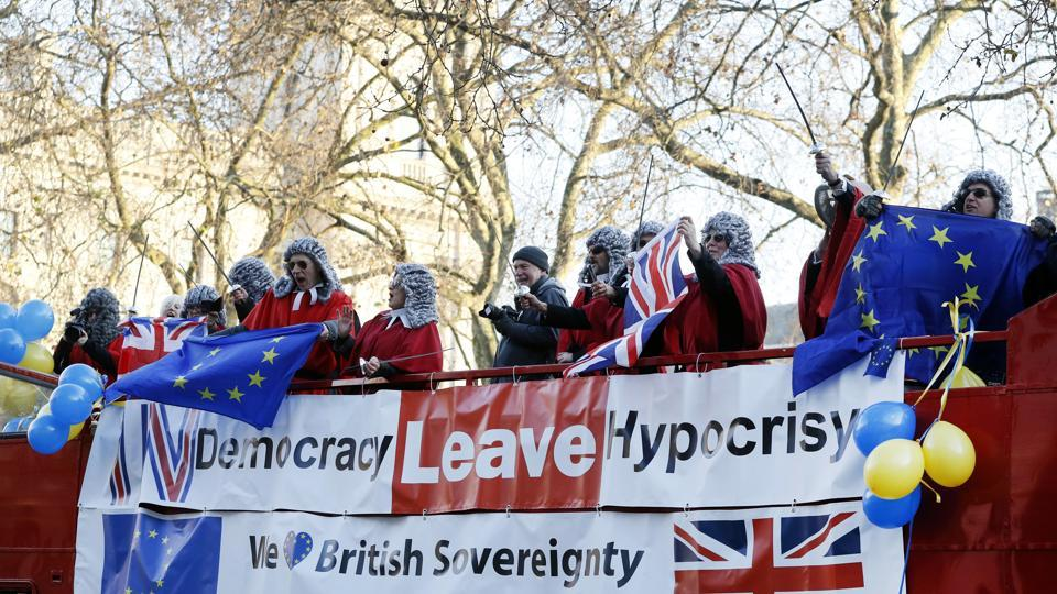 Demonstrators dressed in costume wave flags from the top of a bus outside The Supreme Court in London.