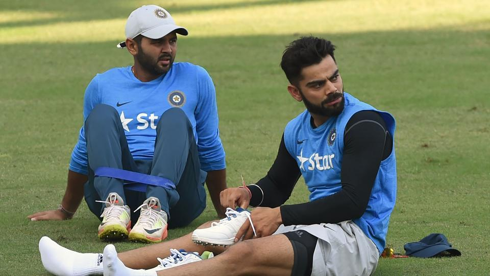 India's captain Virat Kohli (R) and Parthiv Patel watch teammates during the training session. (AFP)