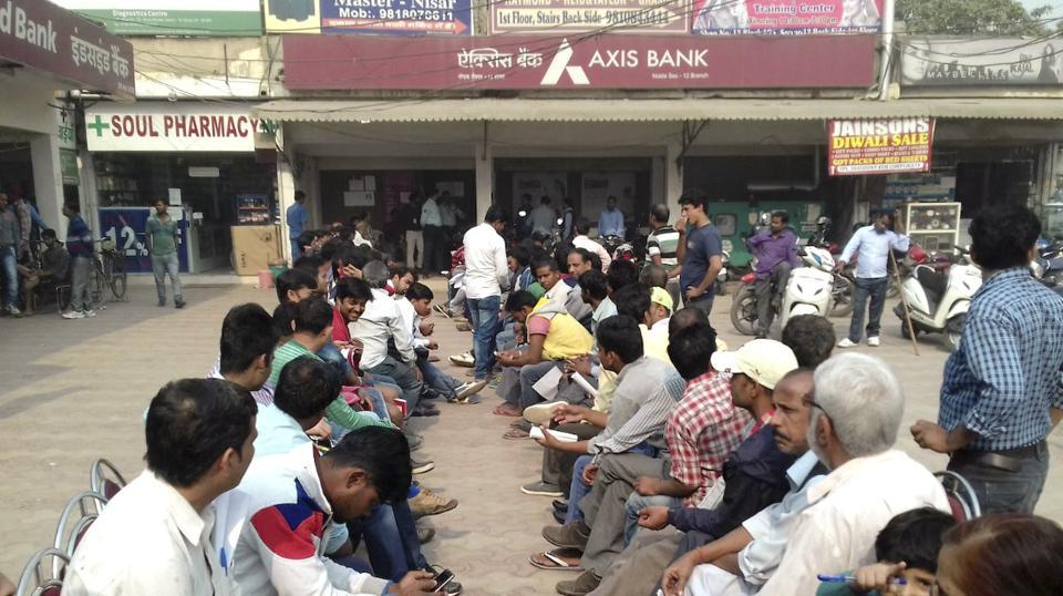 People wait outside an Axis Bank branch in Noida.  The bank has suspended 19 employees across India including 6 in Delhi's Kashmere Gate branch over alleged involvement in illegal practices, post demonetisation.