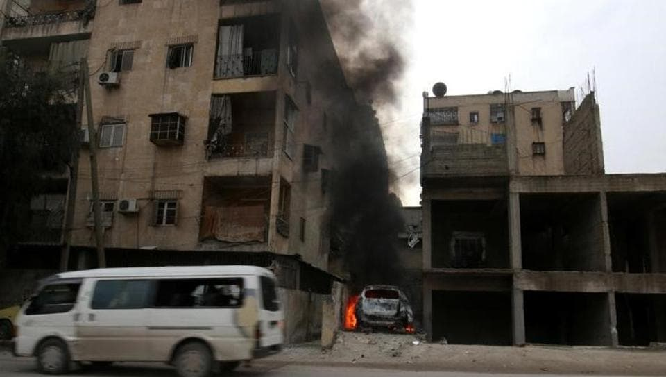 Smoke rises from a car after strikes on the rebel-held besieged al-Zebdieh district, in Aleppo on December 5.