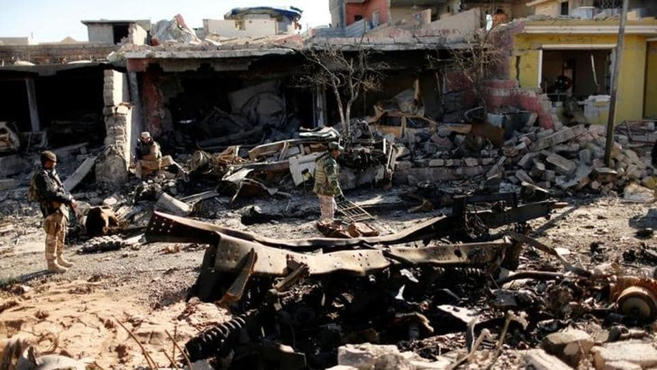 Iraqi soldiers walk among wreckage of buildings damaged from clashes in the frontline during a battle with Islamic State militants in Intisar, eastern Mosul.