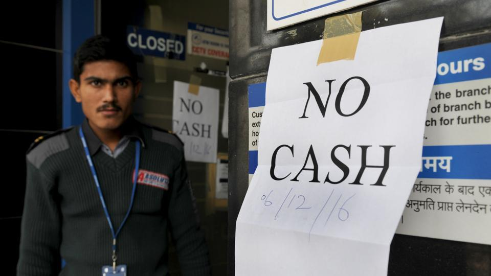A security guard stands outside an ATM displaying 'no cash' notice, in Gurgaon.