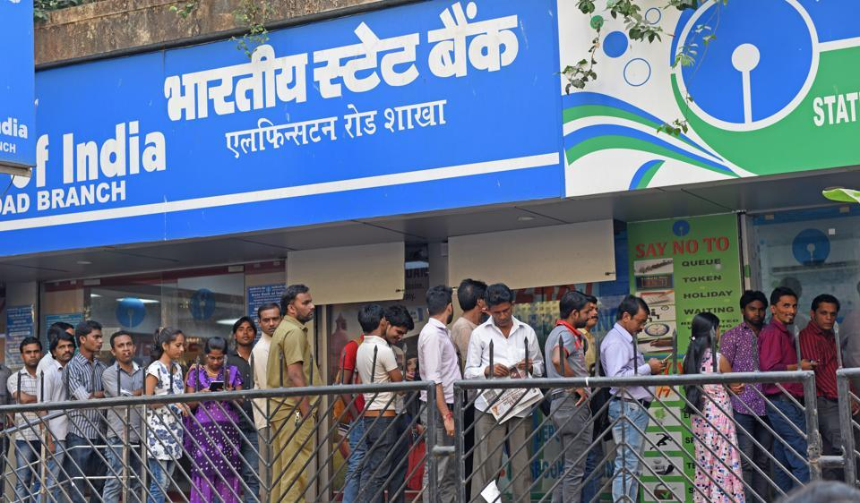 People queue up outside an SBI branch and ATM at Elphinstone Road in Mumbai on Tuesday.