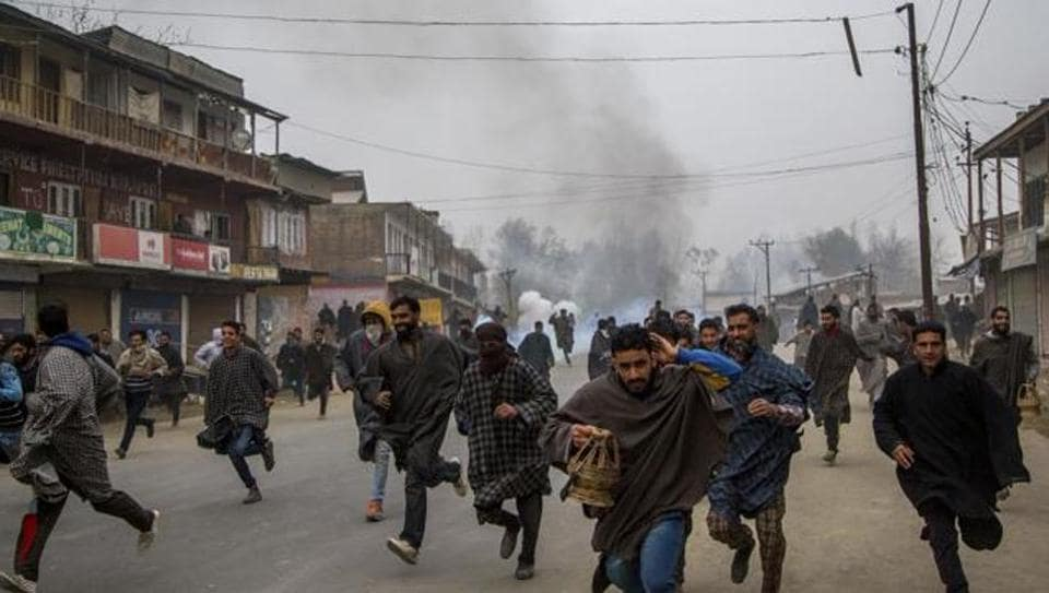 Kashmiri villagers run for cover from tear gas shells and pellets as security forces attempt to dispel protesters near the funeral of Rayees Ahmad Dar, a suspected militant, in Kakpora village south of Srinagar, Kashmir, on November 20, 2016.
