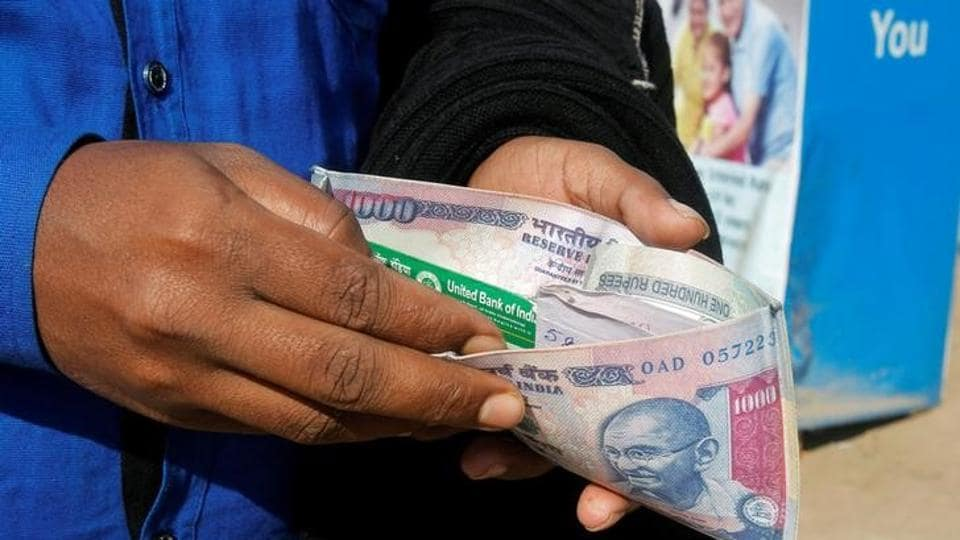 A man puts his debit card inside an Indian currency printed wallet outside a bank in Agartala, India.