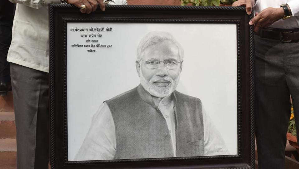 Members of a charitable trust carry a portrait of Prime Minister Narendra Modi to present him at the Parliament House in New Delhi.